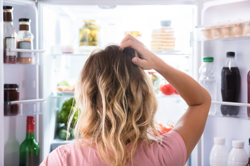 Rear,View,Of,A,Confused,Woman,Looking,In,Open,Refrigerator